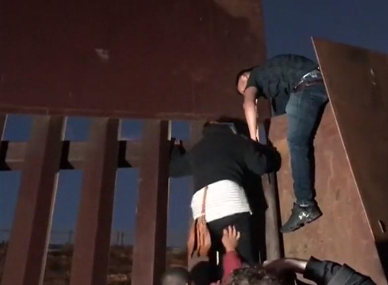 Đoàn di dân leo tường qua biên giới Hoa Kỳ