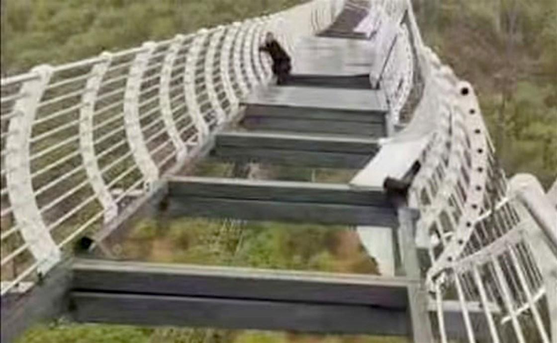 Người đàn ông bám vào cây cầu kính bị vỡ ở miền Bắc Trung Cộng
